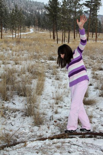 Young brunette teen playing in the field after the snowfall