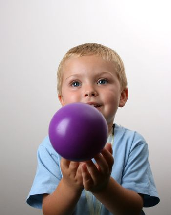 Smiling Blond Toddler catching a purple ball