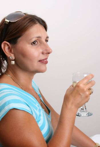 Adult Female Model wearing a blue top with a glass of wine