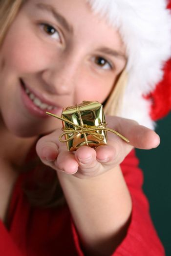 Teenager in red holding a golden gift in her hand. FOCUS ON GIFT
