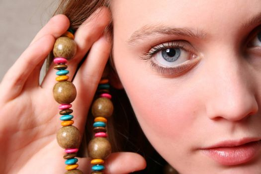 Beautiful female model with blue eyes and a string beads