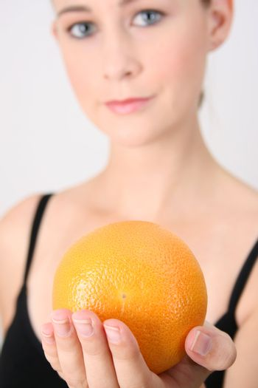 Gym girl holding orange.  FOCUS ON ORANGE