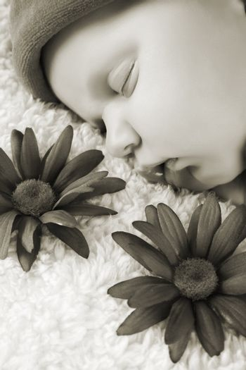 Beautiful newborn baby girl sleeping on a fluffy blanket