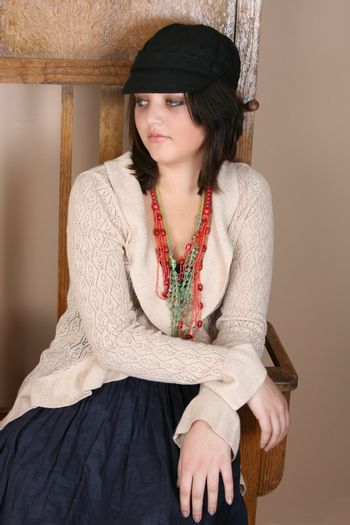 Beautiful teen sitting against an antique coat stand