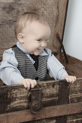 Baby boy playing inside an antique trunk