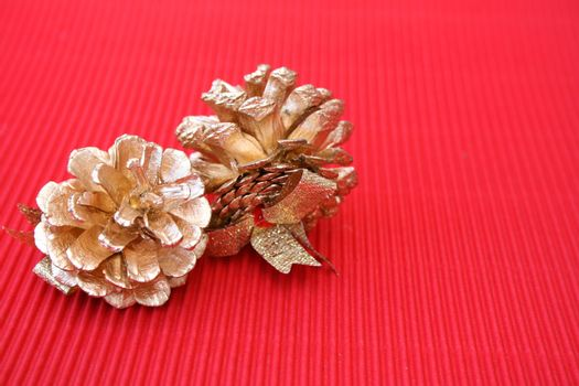 Golden decorated pine cones on a red background