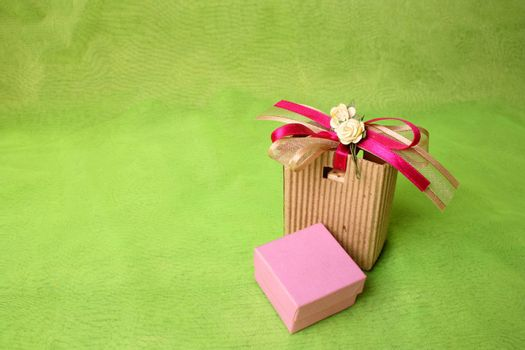 Pink gift box and brown gift bag with ribbons