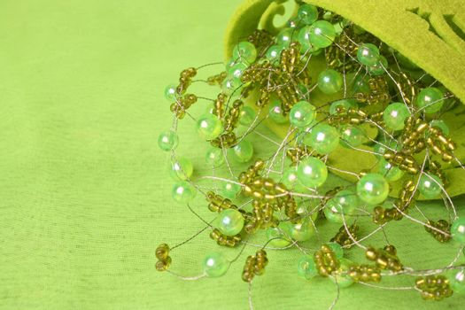 Green beadwork on a green background in a filt cup