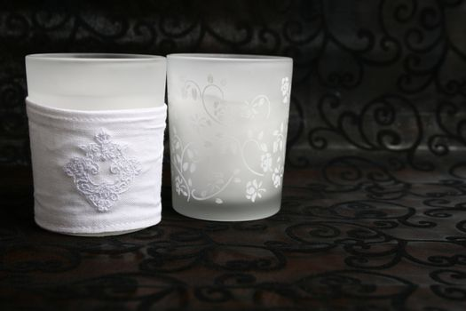 Two white glass holders with candles in