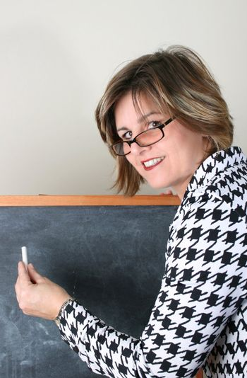 Friendly School Teacher holding white chalk at the blackboard