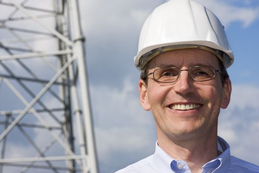 Smiling engineer with hardhat on construction site
