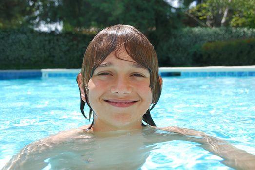 Smiling Teenage Boy Swimming in Pool