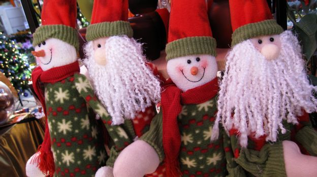 four people in santa claus look are celebrating christmas