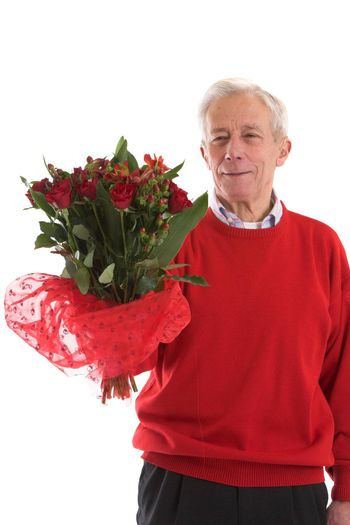 Elderly man holding out a bouquet of flowers for valentine day