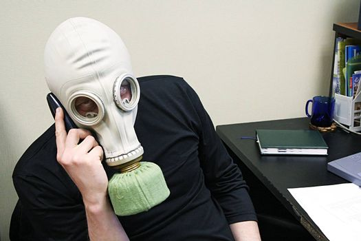 The person in a gas mask speaks by phone