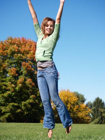 teenage girl jumping in the air on an autumn day