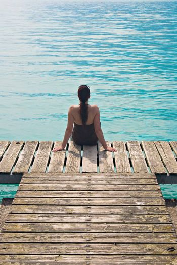 Woman sitting on wooden pier, contemplating a turquoise lake.