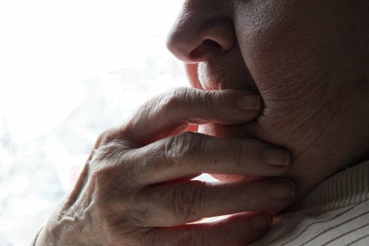 Hand over mouth of elderly woman wondering
