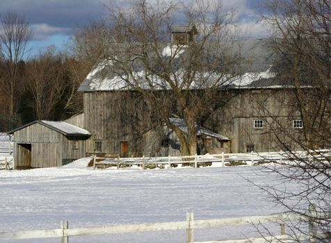 View of a barn surrounded by with winter fields