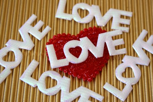 The word love on a golden background on a red heart