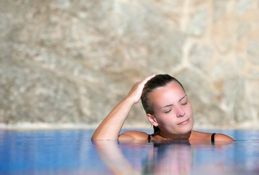 Young woman cools off in pool