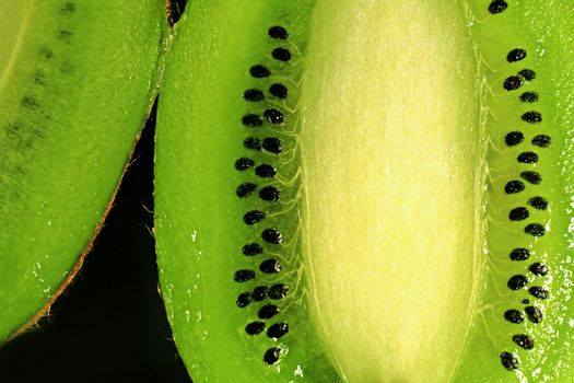 close-up of a kiwi fruit inside with seeds on black