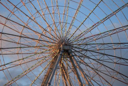 Center of ferris wheel. Spokes radiate outward, deep pink against blue sky