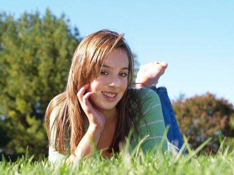 teenage girl laying in the grass on a sunny day