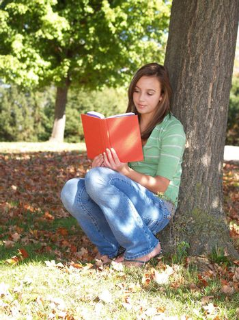 teenage girl sitting by a tree and reading a book