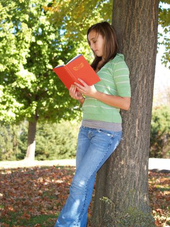 teenage girl standing by a tree and reading a book