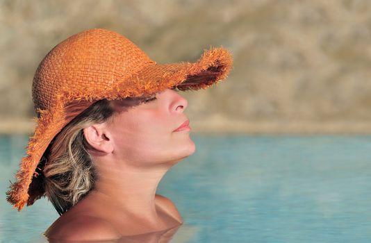 Young woman enjoying the sun in the pool