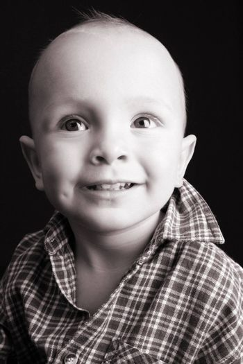 Blonde toddler against a black background with a smile