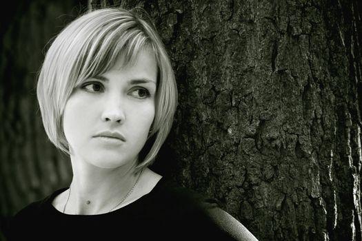 Sad young girl near the tree