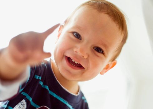 Closeup portrait of little boy smiling on white