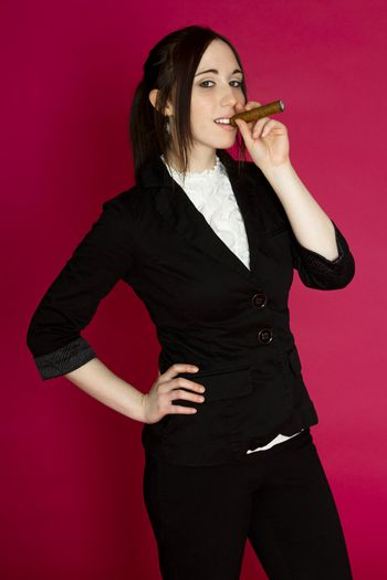 Young woman in a business suit smoking a cigar against a pink background