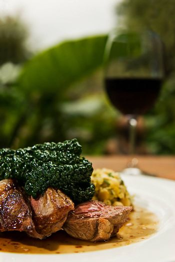 Lamb rump topped with steamed cabbage served with a nice glass of red wine.