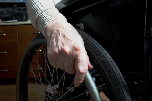 Elderly woman's hand holding wheel from a wheelchair