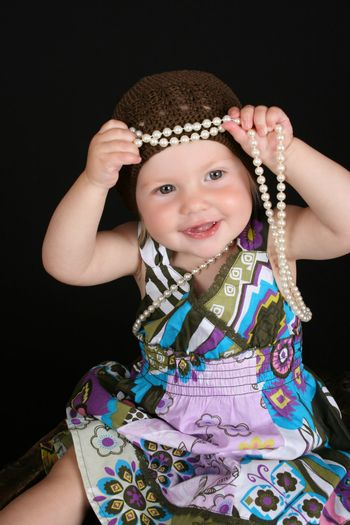 Beautiful little blond girl playing with a string of pearls