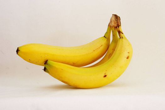 three fresh bananas over a light background
