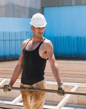 Construction worker carrying reinforcement steel bars
