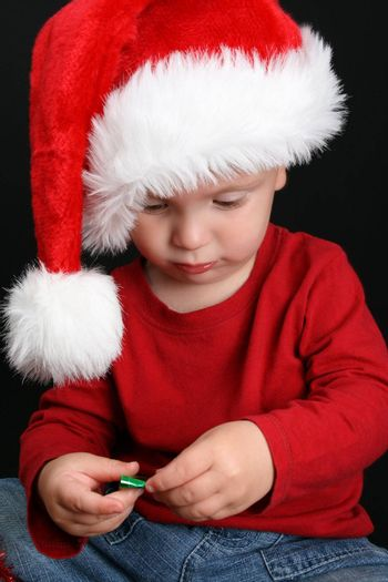 Blonde toddler against a black background with a christmas hat