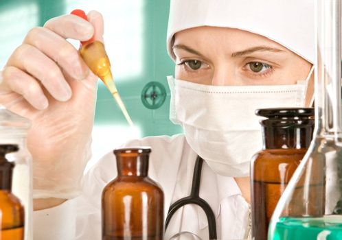 The woman-doctor with concentration drips from a pipette in a small bottle near a table on which there is a flask with a greenish liquid