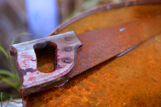 Rusted old saw tool over rusty background