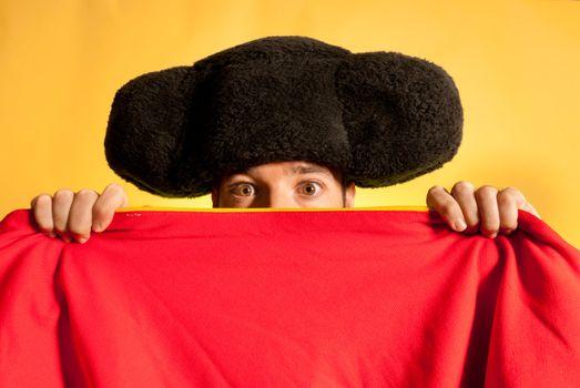 Bullfighter afraid with big montera hidden behind cape humor spanish colors