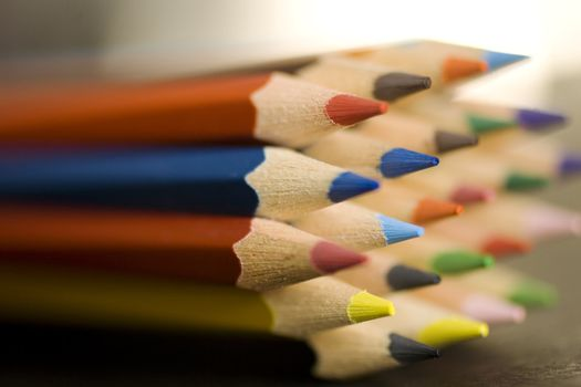 Close up of group of multi-colored coloring pencils isolated on blsck background.