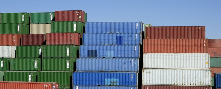 Stacked freight colorful containers, blue sky