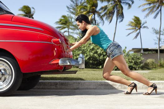 woman pushing broken down old car