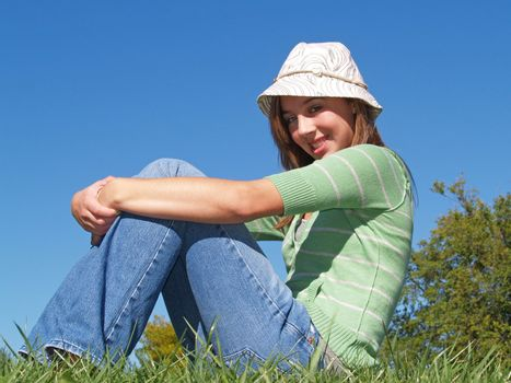 teenage girl sitting in the grass on a sunny day