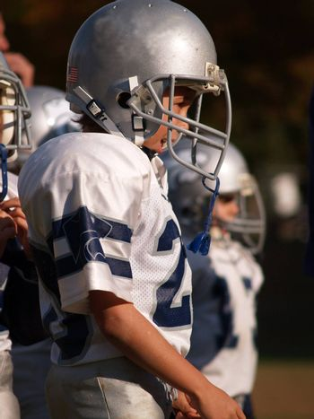 young American football player waiting on the sideline to play
