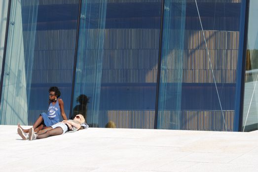 Young people sun bathing at the roof of Oslo Opera House.